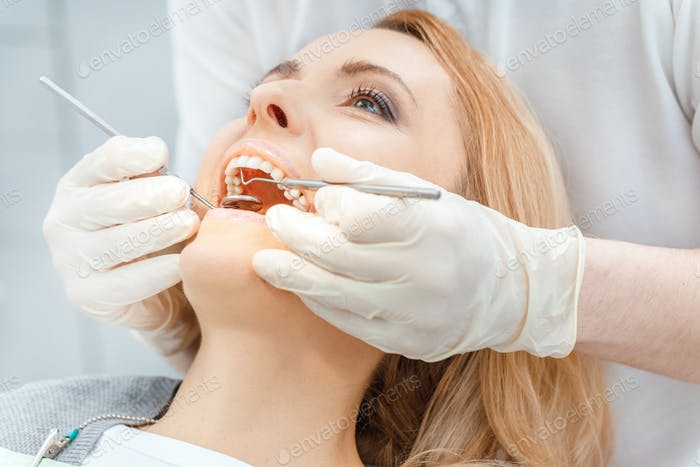 Close-up partial view of beautiful blonde woman at dental check up looking up