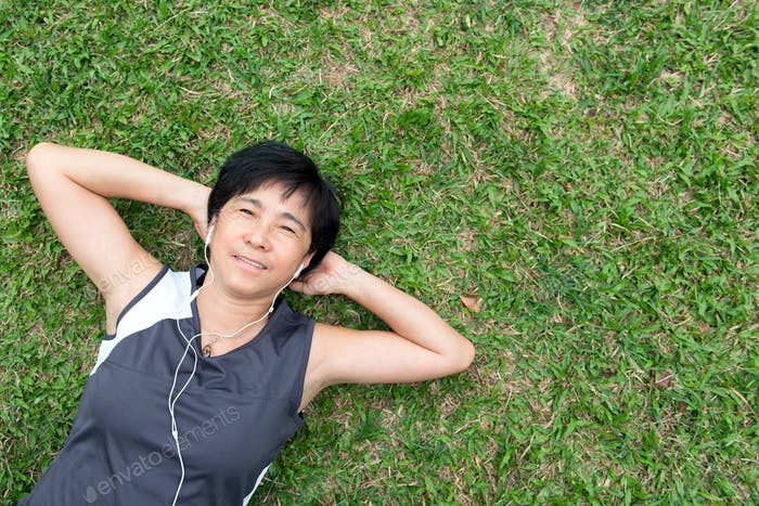 Senior woman laying on the grass