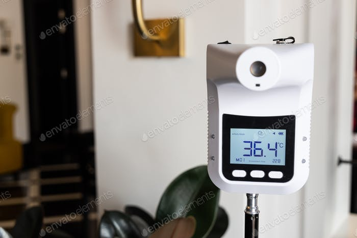 Infrared thermometer at entrance of commercial shop to scan visitor temperature