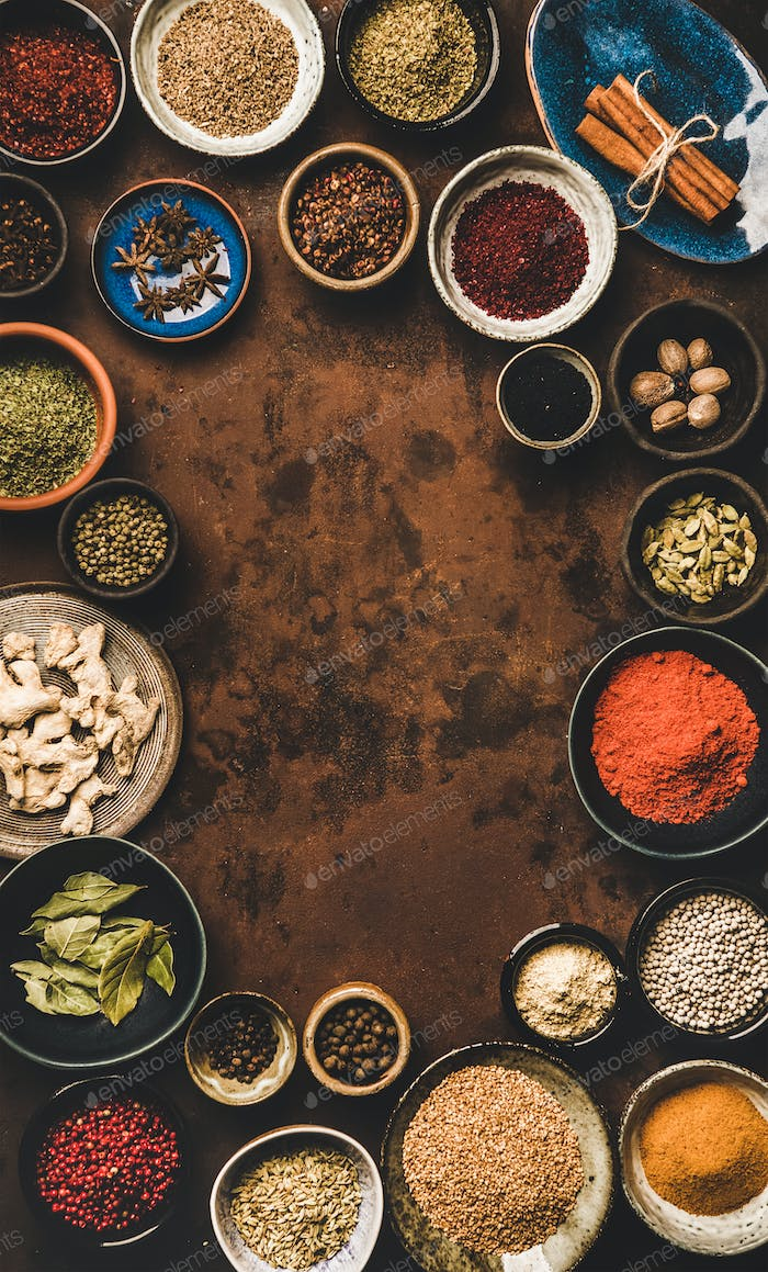 Flat-lay of spices in bowls over rusty background, vertical composition