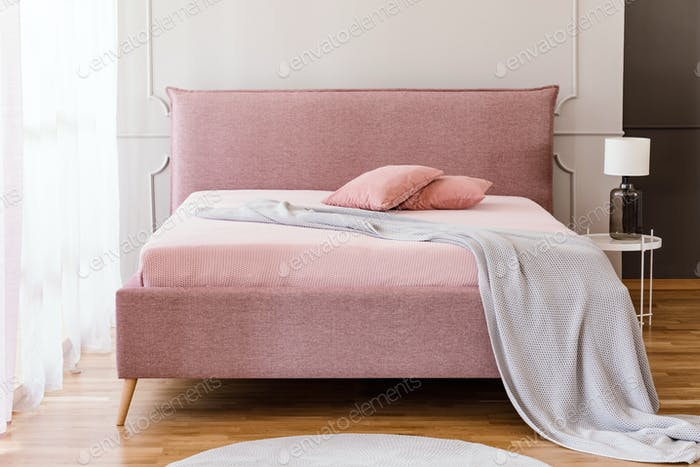 Real photo of pastel pink king-size bed with knit blanket and tw