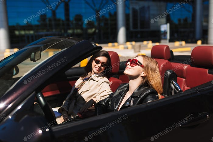 Beautiful girl in sunglasses happily  driving cabriolet car with