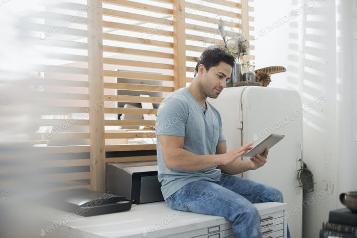 A man sitting on a table using a digital tablet.