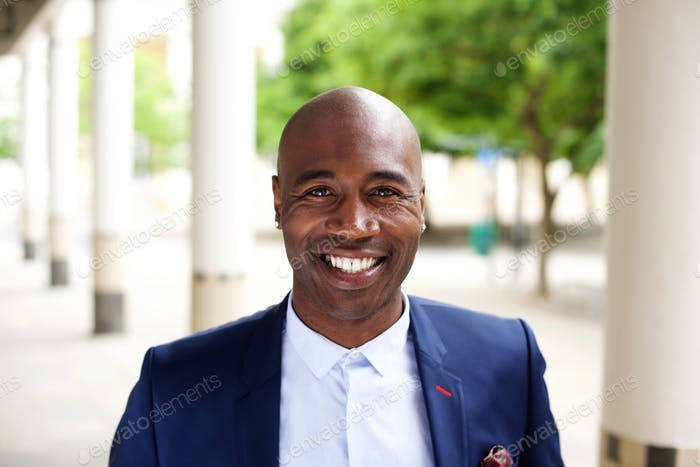 Smiling african businessman standing outdoors
