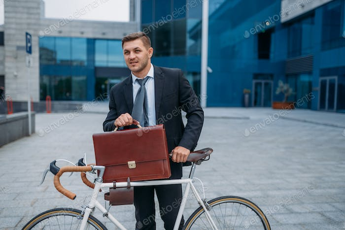 Businessman with bicycle near office building