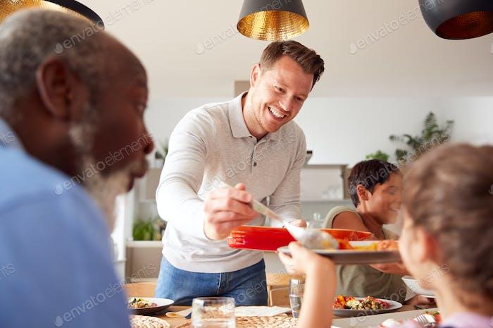 Vater dient als Multi-Generation gemischte Rasse Familie Essen Essen Essen rund Tisch zu Hause zusammen