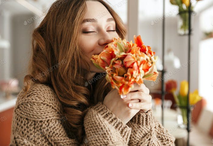 Photo of tender woman in sweater smelling beautiful flower with