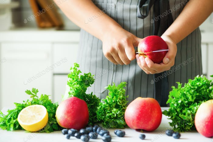 Woman hands cutting, chopping apple for green smoothie. Homemade healthy green smoothie. White