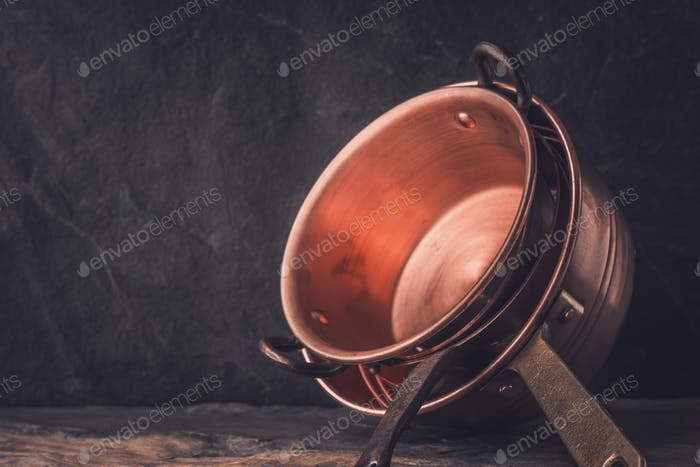 Cooper pots and pans on the stone table horizontal