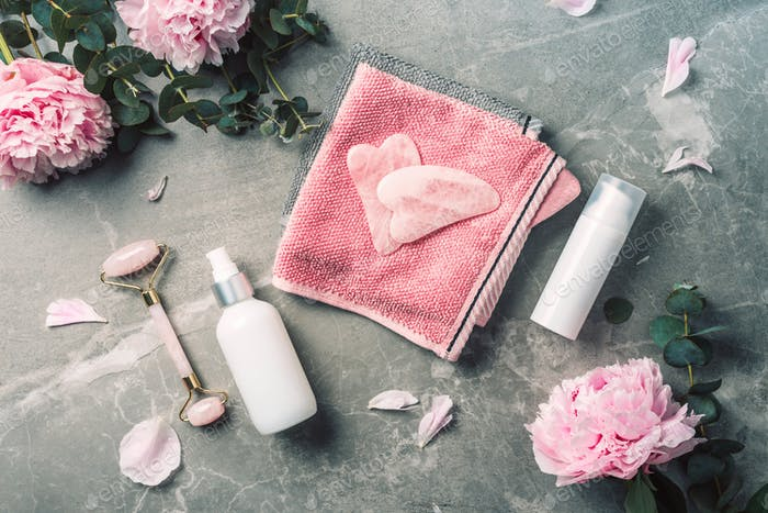 Facial roller, gua sha massager, oil bottle, towel, pink peonies on marble background. Copy space