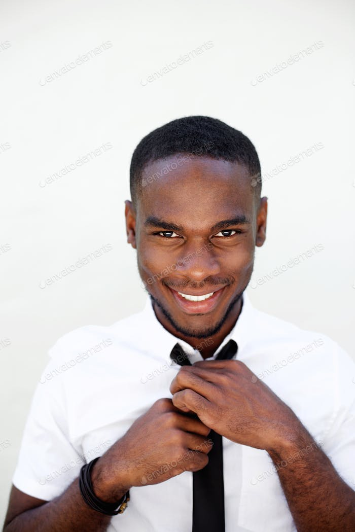 Young african businessman adjusting his tie