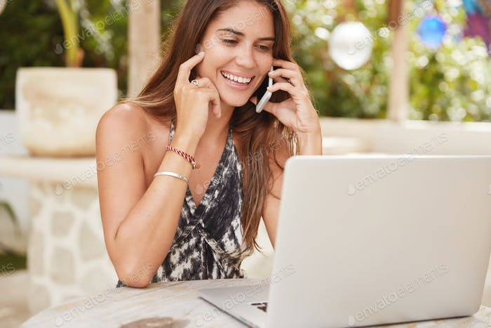 Beautiful female blogger has pleasant talk with friend on mobile phone, enjoys communication, uses a