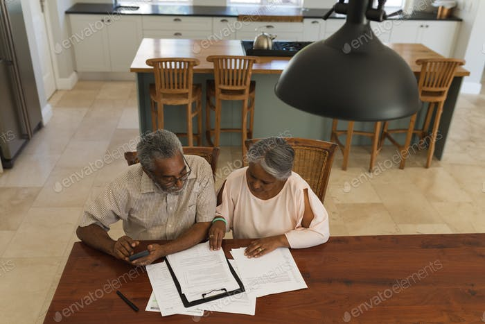 Senior couple discussing over invoices at the table of the living room at home