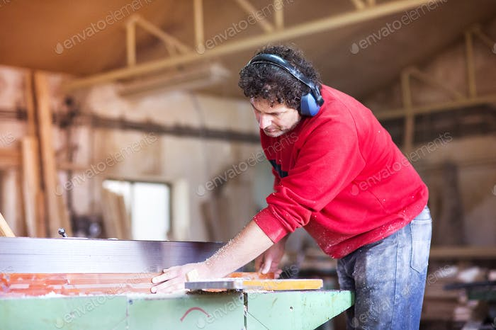 Carpenter working with wood planer