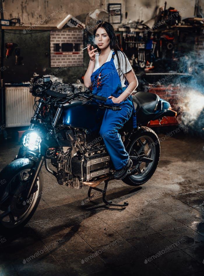 Красивая брюнетка женщина-механик курит сигарету сидит на заказ боббер в гараже
