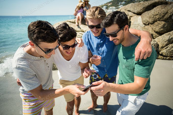 Cheerful male friends looking in smartphone