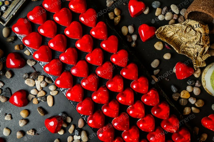 top view chocolates in the shape of a red heart on a stand with pebbles