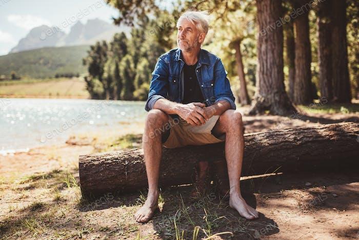 Senior Mann sitzt auf einem Baumstamm in der Nähe von See