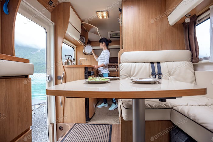 Woman cooking in camper, motorhome interior