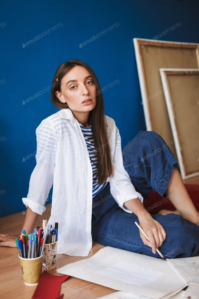 Pensive painter in white shirt and striped T-shirt sitting on fl