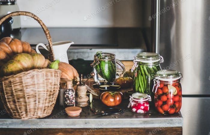 Fresh ingredients and glass jars with homemade vegetables preserves, close-up
