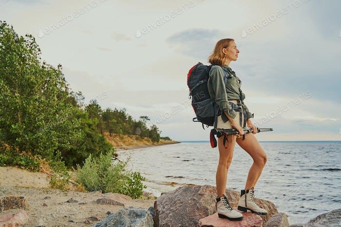 Sportive woman standing on rocks at riverside