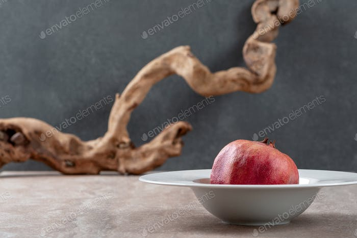 Conceptual food photography background: pomegranate in a white p
