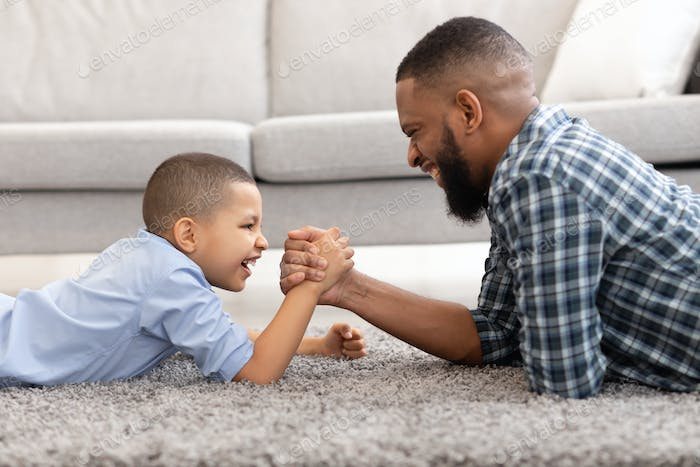 African Father And Son Arm Wrestling Lying On Floor Indoors