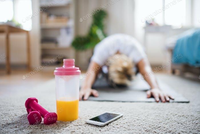 Junge Frau, die Übung auf dem Boden drinnen zu Hause macht.
