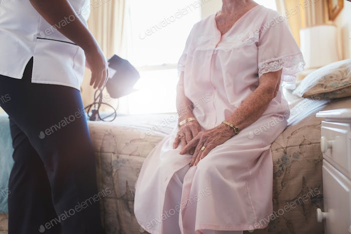 Home caregiver with senior woman sitting on bed