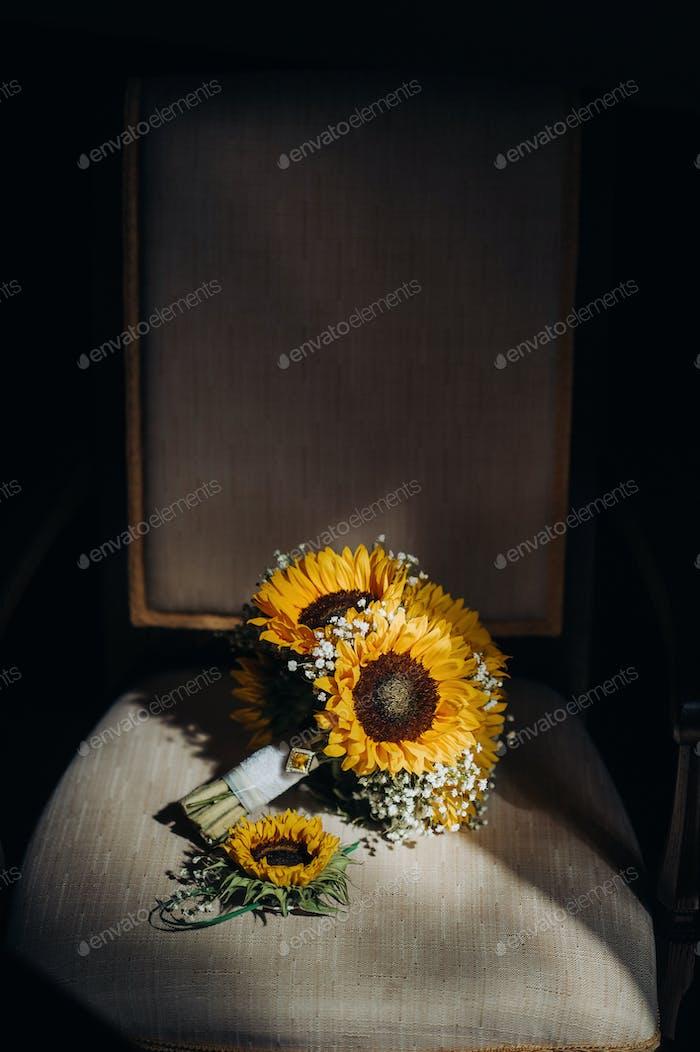 a wedding bouquet of sunflowers lies on an antique chair.Wedding Decor
