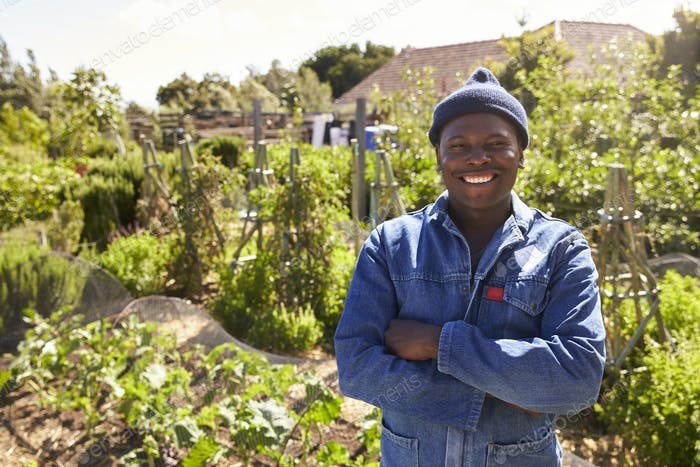 Portrait Of Gardener Standing In Community Allotment