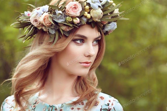 Schöne blonde Frau mit Blumenkranz auf ihrem Kopf