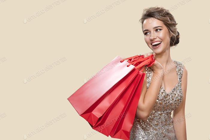 Portrait Of Happy Charming Woman Holding Red Shopping Bags.