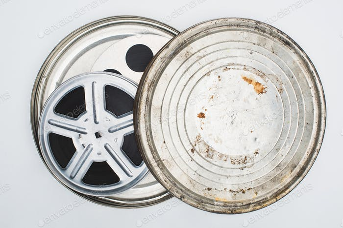 Top View of Film Reels With Tape in Rusty Tin Case on White Background