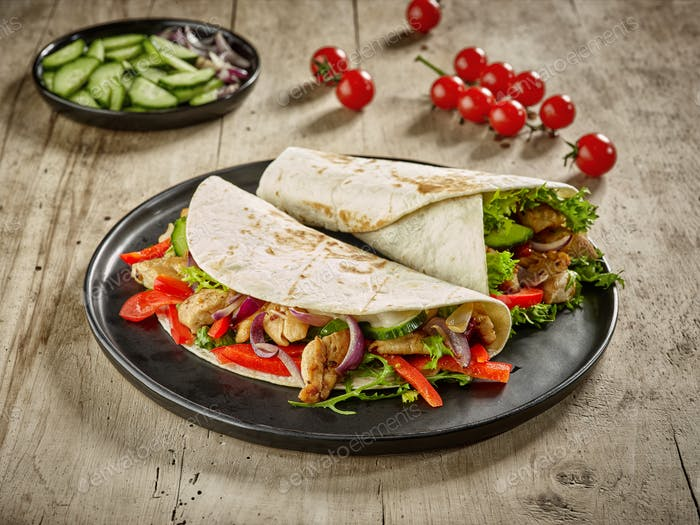 Tortilla wraps with fried chicken meat and vegetables