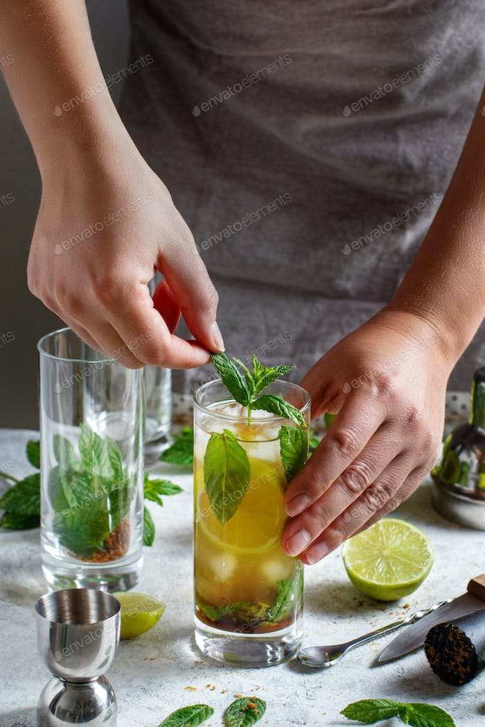 Hands adding fresh mint in glass with Mojito cocktail