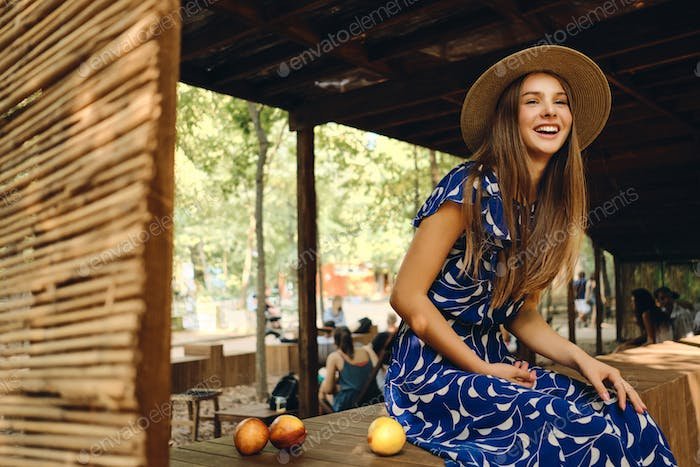 Pretty cheerful girl in dress and hat happily sitting with delicious peaches in park