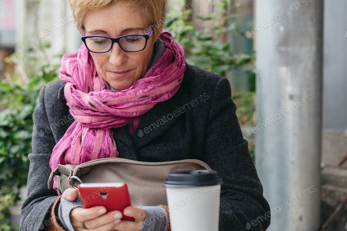 Adult woman with coffee and smartphone