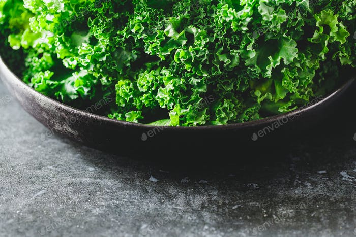 Fresh curly kale salad in a black plate