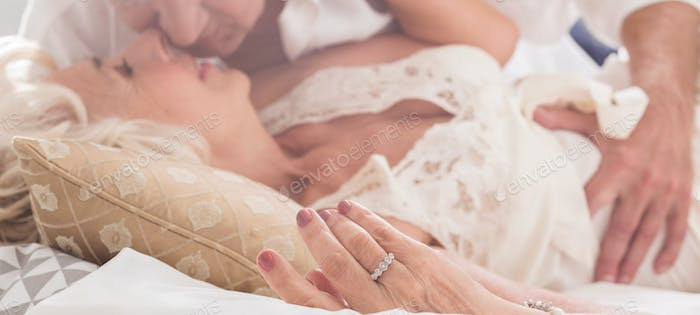 Elderly couple kissing in bed
