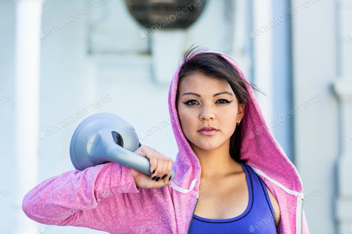 Portrait of athletic woman holding kettlebell in the city