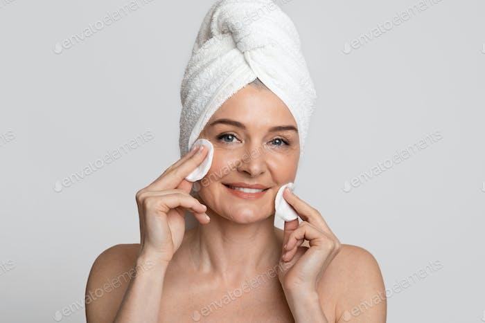 Schöne Frau mittleren Alters Reinigung ihr Gesicht mit Toner und Wattepads