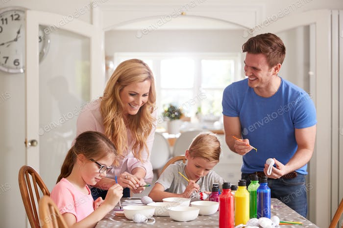 Parents With Children Sitting At Table Decorating Eggs For Easter At Home