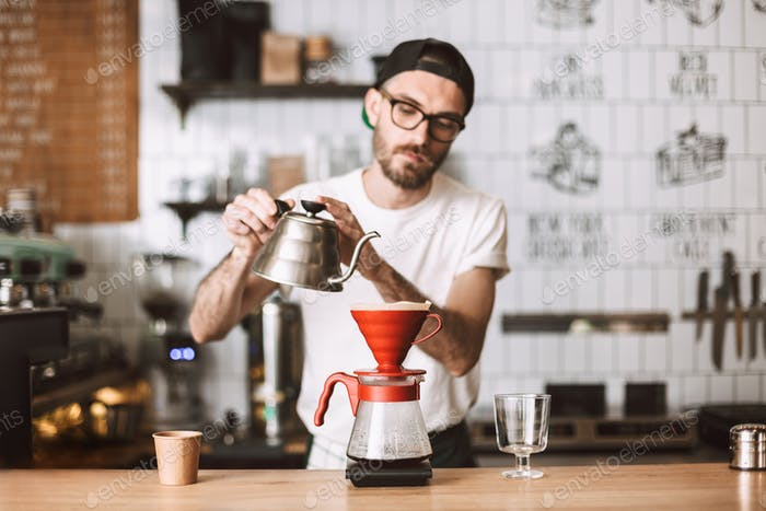 Barista in eyeglasses and cap standing at counter preparing pour over coffee working in cafe