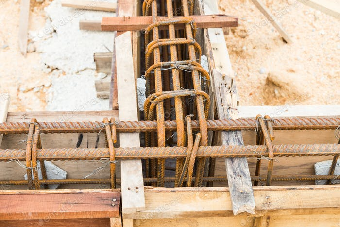 Close up of wooden mold with steel rod forming the foundation beam at construction site