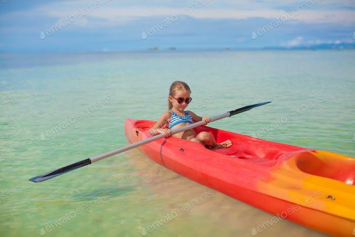 Kleine entzückende Mädchen Rudern ein Boot in blau klares Meer