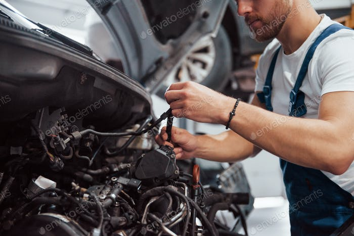 Wire for clutch in hands. Employee in the blue colored uniform works in the automobile salon