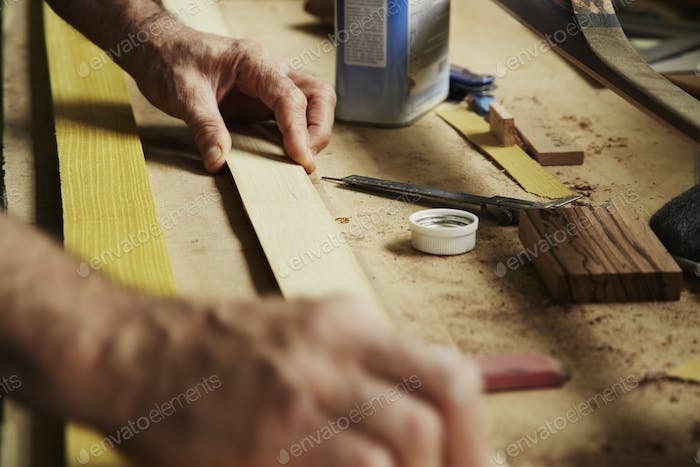 A carpenter at a workbench holding a piece of wood.