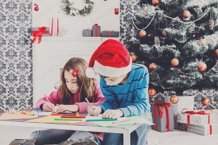 Cute children writing letter to santa, wait for christmas